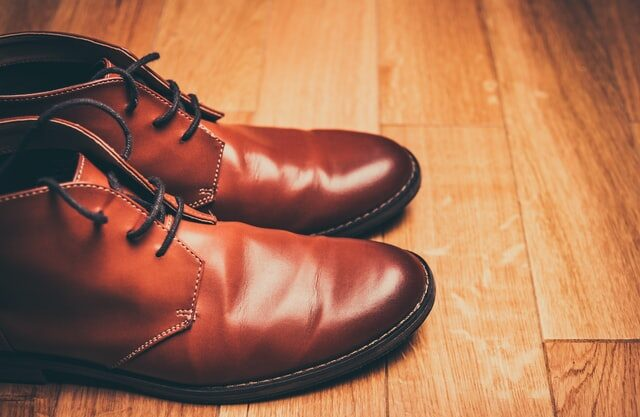 Brown leather shoes on a wooden floor to show bata is not an indian brand